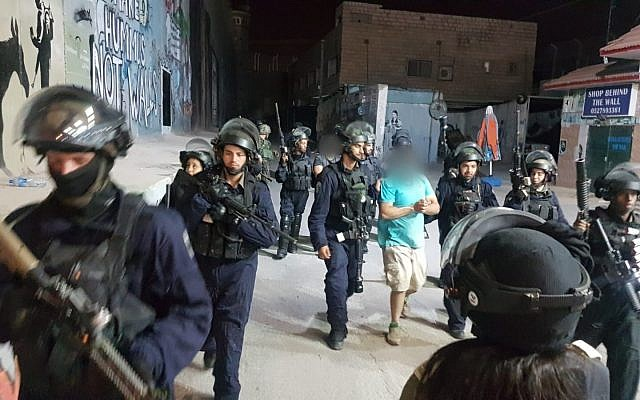 Illustrative: Members of Israeli security forces arrest a Palestinian suspected of hurling a pipe bomb at Rachel's Tomb, in the al-Ayda refugee camp in the West Bank, on October 4, 2018. (Israel Police)
