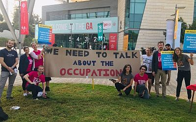 All That's Left activists stand in front of a banner reading, 'We need to talk about the occupation,' at the Jewish Federations of North America General Assembly in Tel Aviv, Wednesday, October 24, 2018. (Steven Davidson/ Times of Israel)