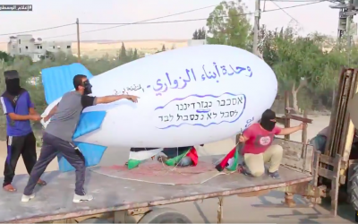 Palestinians transport an incendiary blimp to launch over the Gaza border into Israel on October 13, 2018. (screen capture: Twitter)