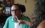 A man with multiple sclerosis gets help drinking water, August 21, 2015. (AP Photo/Brennan Linsley)