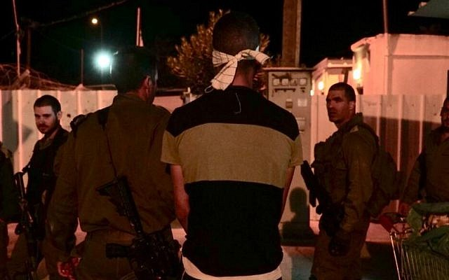 Israeli soldiers arrest the suspect in the stabbing of an army reservist outside an IDF base in the northern West Bank, October 12, 2018. (Nasser Ishtayeh/Flash90)