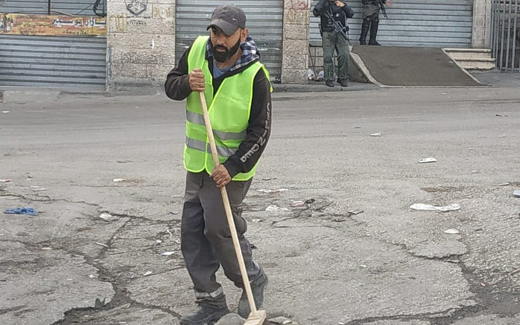 A Jerusalem sanitation worker sweeps a street in the Shuafat refugee camp on October 23, 2018. (Jerusalem municipality)