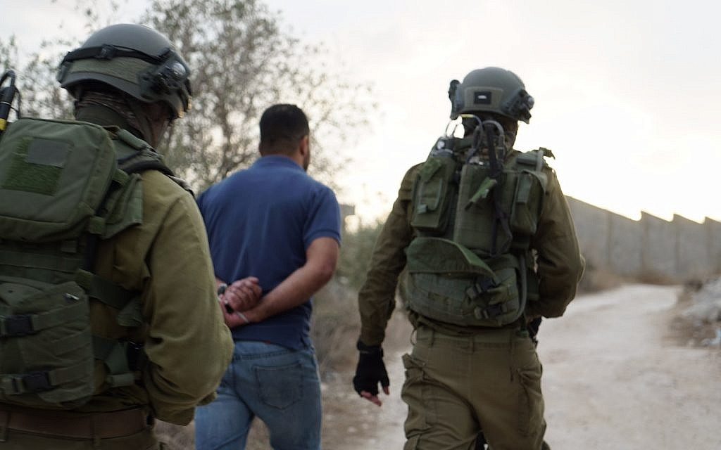 Israeli troops lead away a detained man during operations in the northern West Bank village of Shuweika on October 7, 2018. (Israel Defense Forces)