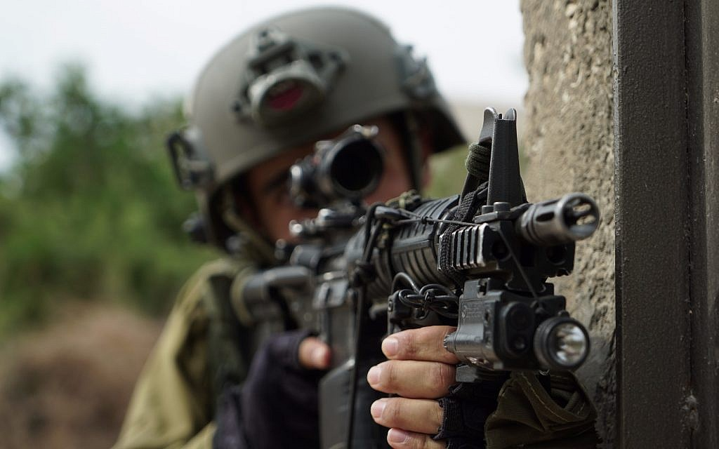 An Israeli soldier aims his gun during operations in the northern West Bank village of Shuweika on October 7, 2018. (Israel Defense Forces)