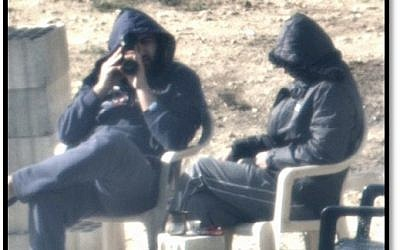 Lebanese men, whom the IDF says are members of the Hezbollah terrorist group, peer into Israel from an observation post near the border, as seen in images released by the military on October 22, 2018. (Israel Defense Forces)