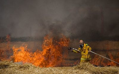 Israeli firefighters extinguish a fire in a wheat field caused by kites flown by Palestinian protesters, near the border with the Gaza Strip, May 30, 2018. (Yonatan Sindel/Flash90)
