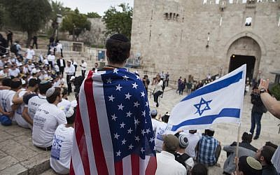 A man wearing an American flag watch the flags march outside Damascus Gate on May 13, 2018 in Jerusalem, Israel. (Lior Mizrahi/Getty Images via JTA)