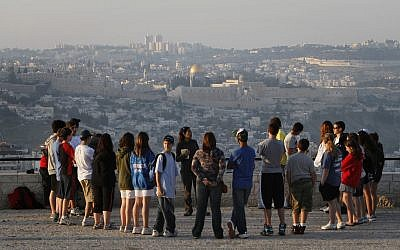 A tour group listens to a guide at the Armon Hanatziv Promenade in Jerusalem against the backdrop of the Old City in 2018 (Miriam Alster/Flash90)