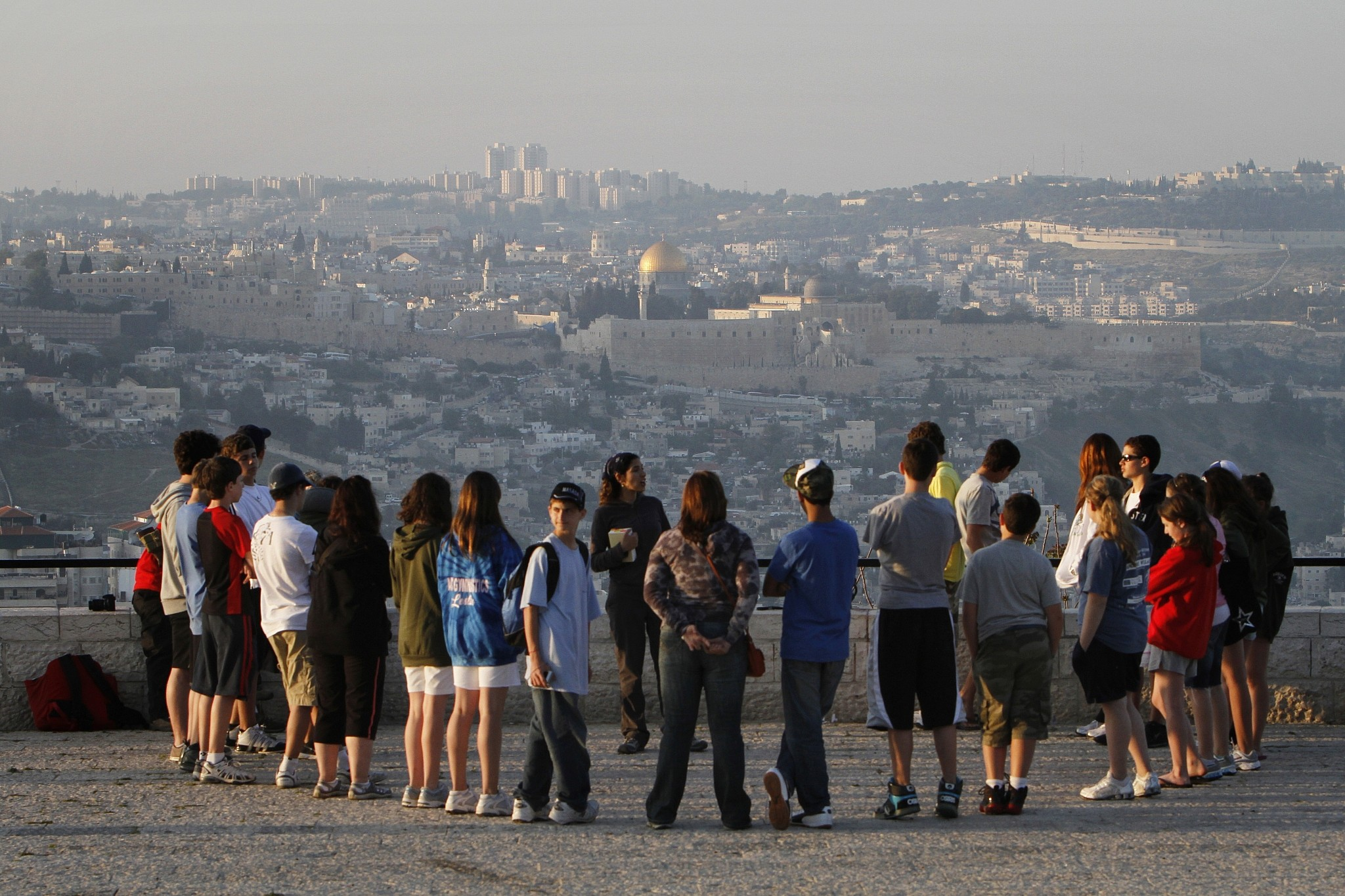 A tour group listens to a guide at the Armon HaNatziv Promenade in Jerusalem against the backdrop of the Old City, April 14, 2010. (Miriam Alster/Flash90)