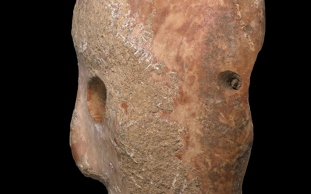 Side view of a 9,000-year-old stone mask discovered in the southern Hebron Hills area of the West Bank in early 2018. (Clara Amit, Israel Antiquities Authority)