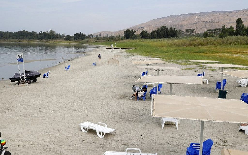 People sit on the beach of the Sea of Galilee near Kibbutz Ein-Gev, on October 8, 2018. (JACK GUEZ/AFP)