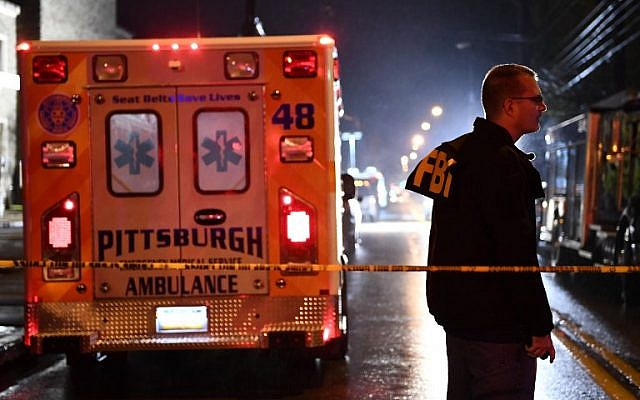 An FBI agent stands behind a police cordon and an ambulance outside the Tree of Life Synagogue (L) after a shooting there left 11 people dead in the Squirrel Hill neighborhood of Pittsburgh on October 27, 2018. (Brendan Smialowski / AFP)