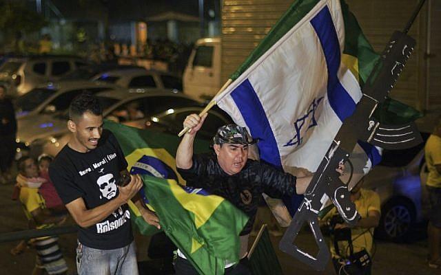 Apoiadores do parlamentar de extrema direita e candidato à presidência pelo Partido Social Liberal, Jair Bolsonaro, celebram no Rio de Janeiro, depois que o ex-capitão do exército venceu a eleição presidencial no Brasil, em 28 de outubro de 2018. (CARL DE SOUZA / AFP)