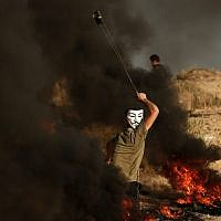 Illustrative: A Palestinian uses a slingshot to hurl stones during clashes on a beach near the maritime border with Israel, in Beit Lahia in the northern Gaza Strip, on October 29, 2018. (Mahmud Hams/AFP)
