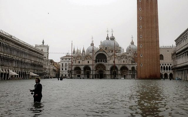 A man walks in the flooded St. Mark's Square during a high-water (Acqua Alta) alert in Venice on October 29, 2018. (MIGUEL MEDINA / AFP)