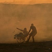 A Palestinian pulls another Palestinian on a wheelchair amid clouds of tear gas fired by Israeli forces during clashes east of Gaza City near the Israeli border on November 2, 2018. (Mahmud Hams/AFP)