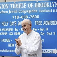 Rabbi Mark Sameth gestures as he thanks members of the Brooklyn Jewish community while NYPD officers stand guard at the door of the Union Temple of Brooklyn on November 2, 2018 in New York City. New York police were investigating anti-Semitic graffiti found inside the synagogue that forced the cancellation of a political event less than a week after the worst anti-Semitic attack in modern US history. (Photo by KENA BETANCUR / AFP)