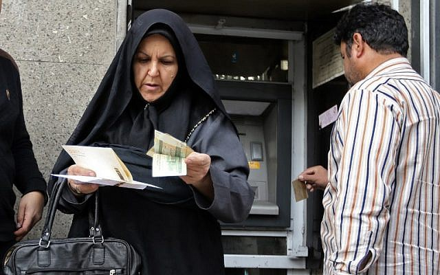 People withraw money from an automated teller machine in the Iranian capital Tehran's grand bazaar on November 3, 2018. (ATTA KENARE / AFP)