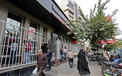 Iranians walk past a bank in the capital Tehran on November 3, 2018. (ATTA KENARE / AFP)