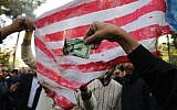 On the eve of renewed sanctions by Washington, Iranian protesters burn a dollar banknote and a US makeshift flag during a demonstration outside the former US embassy in the Iranian capital Tehran on November 4, 2018, marking the anniversary of its storming by student protesters that triggered a hostage crisis in 1979. (ATTA KENARE / AFP)