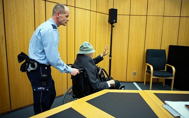 A justice officer pushes the 94-years-old defendant, a former SS guard, in a wheelchair to the courtroom for his trial at the regional court in Muenster, western Germany, on November 6, 2018. The man's face has been blurred at the request of the German court. (Guido Kirchner/dpa/AFP)