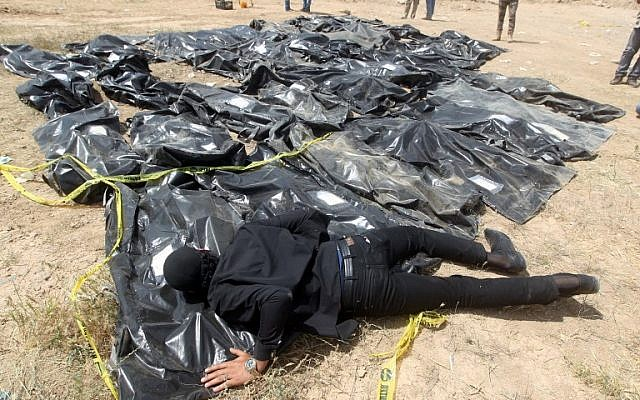 In this photo taken on April 12, 2015, an Iraqi man cries over body bags containing the remains of people believed to have been slain by Islamic State jihadists at the Speicher camp in the Iraqi city of Tikrit. (AHMAD AL-RUBAYE / AFP)