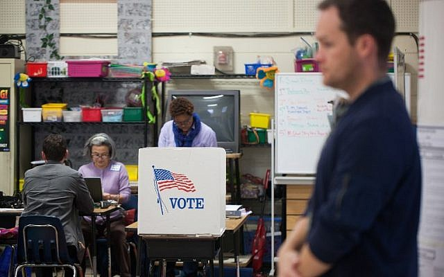 Election workers assist would-be voters at First Ward Creative Arts Academy on November 6, 2018 in Charlotte, North Carolina. (Logan Cyrus / AFP)