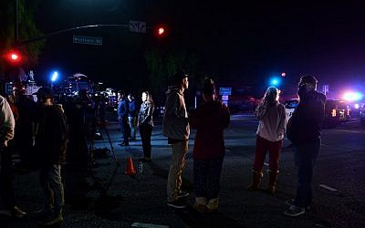 People stand and watch as the scene unfurls from the intersection of US 101 freeway and the Moorpark Rad exit as police vehicles close off the area outside a country music bar and dance hall in Thousand Oaks, west of Los Angeles, where a gunman opened fire late November 7, 2018, killing at least 12 people, US police said. (Photo by Frederic J. BROWN / AFP)