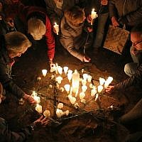 People light candles on November 8, 2018 at the site of a former synagogue in Schwerin as Germany marks the 80th anniversary of the 'Night of Broken Glass' (Kristallnacht) on November 9, 1938. (Bernd Wuestneck/dpa/AFP)