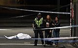 A police officer directs people away from the crime scene as a body is seen covered with a white sheet in Melbourne on November 9, 2018 (Photo by WILLIAM WEST / AFP)
