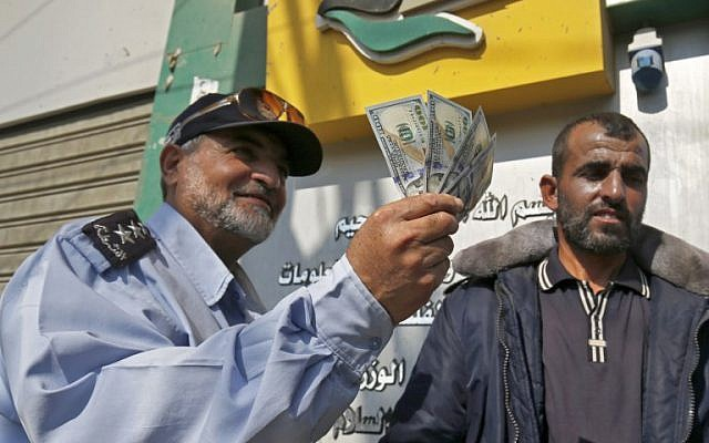 A Palestinian man shows his money after receiving his salary in Rafah in the southern Gaza Strip, November 9, 2018. (Said Khatib/AFP)
