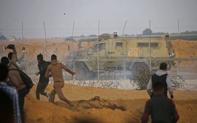 Illustrative: Palestinians hurl rocks at an Israeli army vehicle during clashes the border between Israel and Khan Younis in the southern Gaza Strip on November 9, 2018. (Said Khatib/AFP)