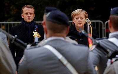 French President Emmanuel Macron and German Chancellor Angela Merkel review troops during a French-German ceremony on November 10, 2018, in the Clairiere of Rethondes in Compiegne, northern France, as part of commemorations marking the 100th anniversary of the 11 November 1918 armistice. (PHILIPPE WOJAZER / POOL / AFP)