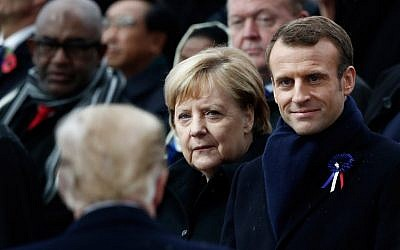 German Chancellor Angela Merkel (C) and French President Emmanuel Macron (R) react as US President Donald Trump (front L) arrives to attend a ceremony at the Arc de Triomphe in Paris on November 11, 2018 as part of commemorations marking the 100th anniversary of the 11 November 1918 armistice, ending World War I. (BENOIT TESSIER / POOL / AFP)