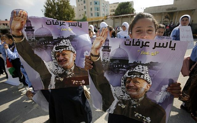 A girl holds a portrait of late leader Yasser Arafat as Palestinians celebrate the 14th anniversary of his death in the the West Bank city of Ramallah, on November 11, 2018. (ABBAS MOMANI/AFP)