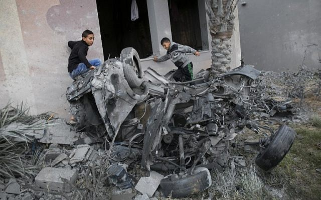 Palestinians stand next to the remains of a car said to be destroyed following an Israeli airstrike, in Khan Younis in the southern Gaza Strip on November 12, 2018 (SAID KHATIB / AFP)