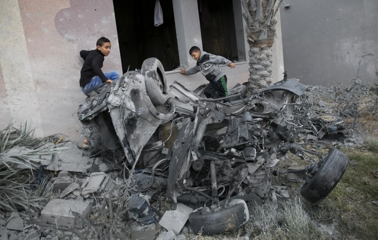 Palestinians stand next to the remains of a car said to be destroyed following an Israeli air strike in Khan Yunis in the southern Gaza Strip
