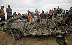 Illustrative: Palestinians stand next to the remains of a car allegedly used by Israeli special forces during an operation in Gaza, which was was later destroyed in an Israeli airstrike, in Khan Younis in the southern Gaza Strip on November 12, 2018. (SAID KHATIB / AFP)