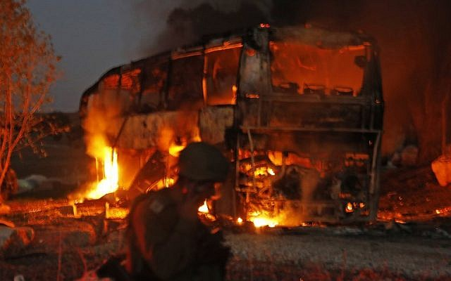 Israeli security forces and firefighters gather near a bus set ablaze after it was hit by a rocket fired from the Palestinian enclave, at the Israel-Gaza border near the kibbutz of Kfar Aza, on November 12, 2018. (Menahem KAHANA / AFP)