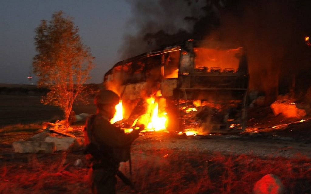 Israeli security forces and firefighters gather near a bus set ablaze after it was hit by an anti-tank missile fired from the Palestinian enclave, at the Israel-Gaza border near the kibbutz of Kfar Aza, on November 12, 2018. (Menahem KAHANA / AFP)