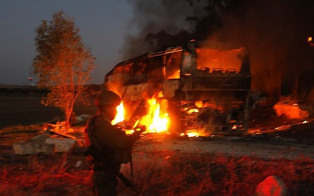 Israeli security forces and firefighters gather near a bus set ablaze after it was hit by an anti-tank missile fired from the Palestinian enclave, at the Israel-Gaza border near the kibbutz of Kfar Aza, on November 12, 2018. (Photo by Menahem KAHANA / AFP)