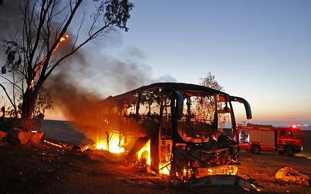 A picture taken on November 12, 2018 shows a bus set ablaze after it was hit by a rocket fired from the Gaza Strip, at the Israel-Gaza border near the kibbutz of Kfar Aza, on November 12, 2018. (Menahem KAHANA / AFP)