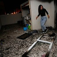An Israeli woman inspects the damage in an apartment that was hit by a rocket fired from the Gaza Strip, in the southern Israeli town of Ashkelon on November 12, 2018. (GIL COHEN-MAGEN / AFP)