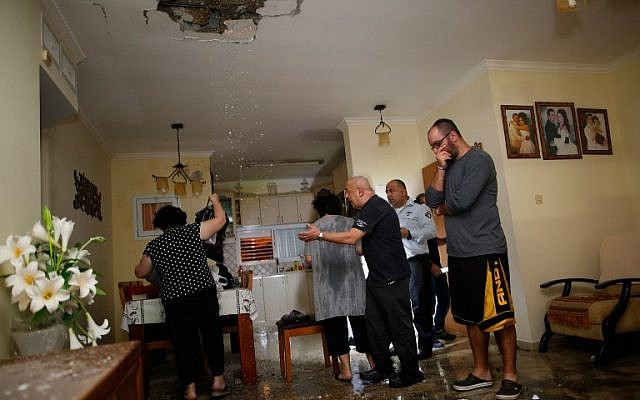 Israelis inspect the damage in an apartment that was hit by a rocket fired from the Gaza Strip, in the southern Israeli town of Ashkelon on November 12, 2018.  (GIL COHEN-MAGEN / AFP)