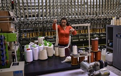A woman works at a silk fabric factory in the Greek northern town of Soufli on October 10, 2018. (Photo by ARIS MESSINIS / AFP)