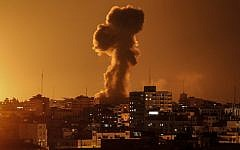 A picture taken on November 12, 2018, shows smoke rising above the building housing the Hamas-run television station al-Aqsa TV in the Gaza Strip during an Israeli air strike.  (Mahmud Hams / AFP)