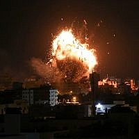 A picture taken on November 12, 2018 shows a ball of fire above the building housing the Hamas-run television station al-Aqsa TV in Gaza City during an Israeli air strike. ( Bashar TALEB / AFP)