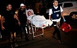 A wounded Israeli woman is evacuated from her apartment, which was set ablaze by a rocket fired from the Gaza Strip, in the southern Israeli city of Ashkelon on November 12, 2018. (Gil Cohen-Magen/AFP)