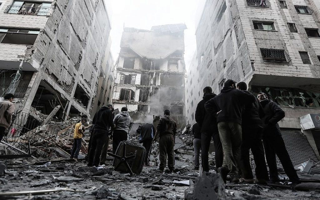 People look at the rubble of a building in Gaza City on November 13, 2018, after an Israeli air strike.  (MAHMUD HAMS / AFP)