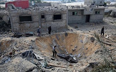 Palestinians inspect a crater caused by an Israeli airstrike earlier this week during fighting with Palestinian terror groups, in Rafah in the southern Gaza Strip, on November 14, 2018. (Said Khatib/AFP)